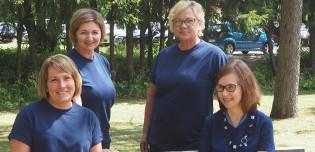 kaksi naista sinisissä paidoissaan istuu puistonpenkillä ja kaksi naista seisoo heidän takanaan.
