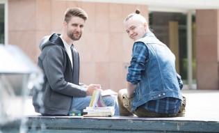 Kaksi miestä istuu Turun yliopiston pihalla.