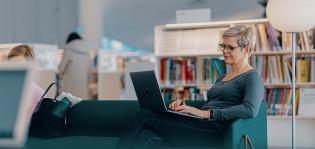 Digituen kuvituskuva, Digi- ja väestötietovirasto. Nainen istuu sohvalla ja käyttää kannettavaa tietokonetta.