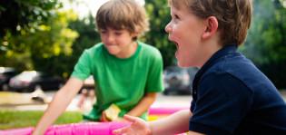 Kaksi poikaa nauraa puistossa