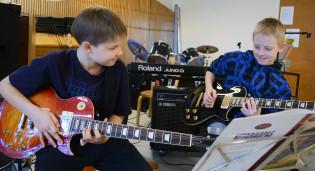 Lapset soittavat kitaraa