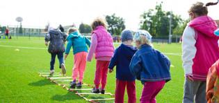 Kuusi lasta urheilukentällä pelaamassa