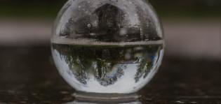 Kuvassa on lasipallo, joka on puolillaan vettä ja josta heijastuu metsän siluetti.