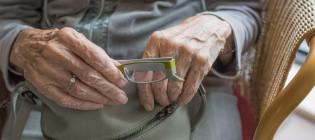 Seniori laittaa silmälasit laukkuun.