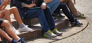 lapsia ja nuoria istuu torilla kiveyksellä ja kuvassa näkyy heidän jalkojaan.