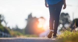 Takaa päin kuvattu nuori kävelemässä kohti valoa
