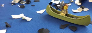 Keltainen legomies poimimassa vedestä (sininen alusta) mustia ja valkoisia roskia (paperipalasia). Legomies istuu vihreässä legoveneessä.