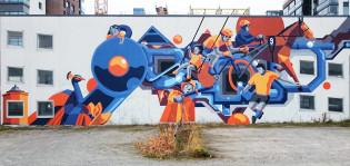 Sinistä ja oranssia yhdistelevä moniulotteinen seinämaalaus kuvaa Kupittaanpuiston historiaa.