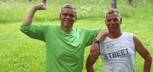 Kaksi miestä nojaavat tosiinsa ja näyttävät iloisilta. Vasemmalla oleva mies näyttää hauista.