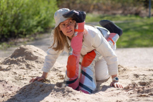 Nainen hiekkalaatikolla kumarassa valkoinen hattu päässä