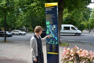 Maija Rusanen katsoo kaupunkiopastetta.
