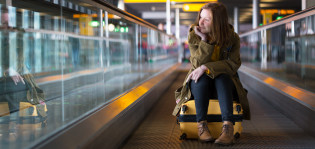 Nuori istuu matkalaukun päällä lentokentän liukutasanteella ja katsoo ikkunasta ulos.