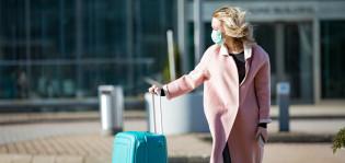Vaaleanpunaisessa takissa rakennuksen edustalla kävelee ja vetää perässään turkoosin väristä matkalaukkua.