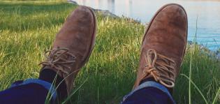 Ihminen nurmikolla ja lähellä vesirajaa, jalassaan farkut ja miehen kuluneet kengät.