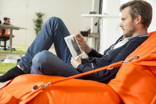 Mies istuu säkkituolissa tabletin kanssa.