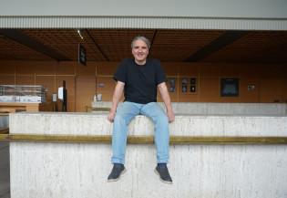 Harmaahiuksinen mies istuu hymyillen porraskaiteella