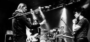 Mikko von Herzen puhuu kolmen nuoren miehen muodostamalle bändille. Kuvan etualalla mikrofoni ja takana näkyvät rummut, joiden takan rumpali istuu.
