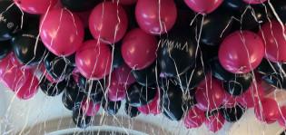 Mustia ja pinkkejä Mimmi Magiaa-tapahtuman heliumilmapalloja katossa