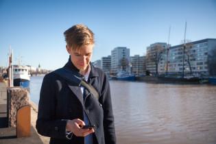 Mobiilikäyttäjä selaa älypuhelintaan joen rannalla