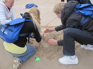 Nuoria rakentamassa hiekasta