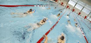 Nuoria kilpauimareita uimassa uimahallin radoilla