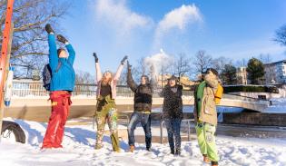 Opiskelijat heittelevät lunta Aurajoen rannassa.