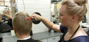 Nuori mies istuu parturissa ja nuori nainen, parturi-kampaajaopiskelija leikkaa hänen hiuksiaan.
