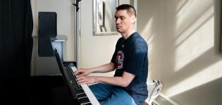 Mies soittaa pianoa pääkirjaston soittohuoneessa.