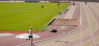 Mies juoksemassa Paavo Nurmen stadionin juoksuradalla