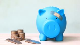 Kolikoita ja laastaroitu säästöpossu