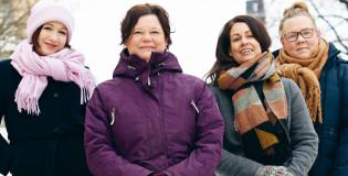 Neljä naista katsoo talvisena päivänä kameraan.