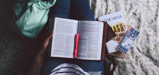 Opiskelija näyttää käsissään olevaa tenttikirjaa.