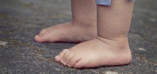 Pieni lapsi seisoo paljain jaloin kalliolla.