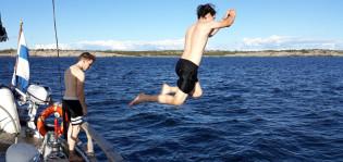 Lukiolaispoika hyppää purheveneen kannelta mereen uimaan. Pojan vasemmalla puolella on toinen poika katsoo veteen. Sää on aurinkoinen.