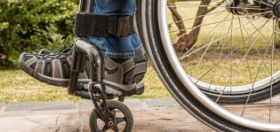 Kuva pyörätuolista ja sen kanssa liikkuvasta.