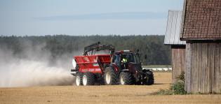 Traktori levittämässä pellolle kalkkia.