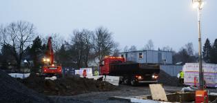 Kaivinkone ja kuorma-auto rakennustyömaalla.