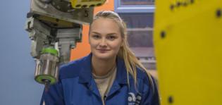 kuvassa naisopiskelija teollisuusrobotin edessä