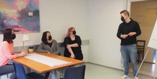 Mies seisoo maski kasvoillaan fläppitaulun edessä. Kolme naista istuu pöydän ääressä.