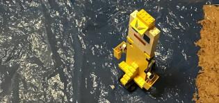 Legoista tehty keltainen roskarobotti mustalla kiiltelevällä alustalla.