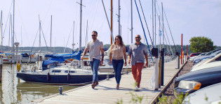 Three persons walking on a dock on a sunny weather. Around them there's many boats berthed.