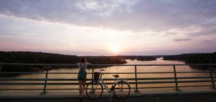 Tyttö pysähtynyt sillalle jo noussut pyörän selästä ihailemaan auringonlaskua. Kaiteeseen nojaavan tytön vieressä valkoinen polkupyörä ja taustalla avautuu saaristomaisema.