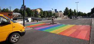 Nainen ylittää katua sateenkaaren väreihin maalatun suojatien kohdalla.