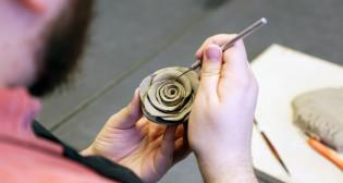 Kädet ja savesta tehty ruusu