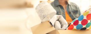 Nainen kantaa pahvilaatikkoa, jossa on erilaisia esineitä