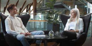 Nuori mies ja nainen juttelevat pöydän ääressä.