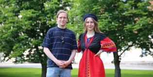 Sinipaitainen nuori mies ja punaiseen mekkoon pukeutunut nuori nainen seisovat rinnakkain ja katsovat kameraan.