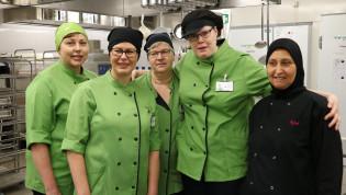 Koulun keittiössä työskentelevät seisovat vierekkäin.