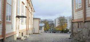 Näkymä koulun pihalle, vanhat puutalot kehystävät kivettyä pihaa. Taustalla modernit kerrostalorakennukset.