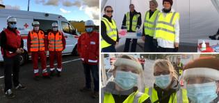 Neljä SPR:n vapaaehtoista seisoo SPR:n pakettiauton edessä liivit päällä ja kasvot suojattuina maskeilla.